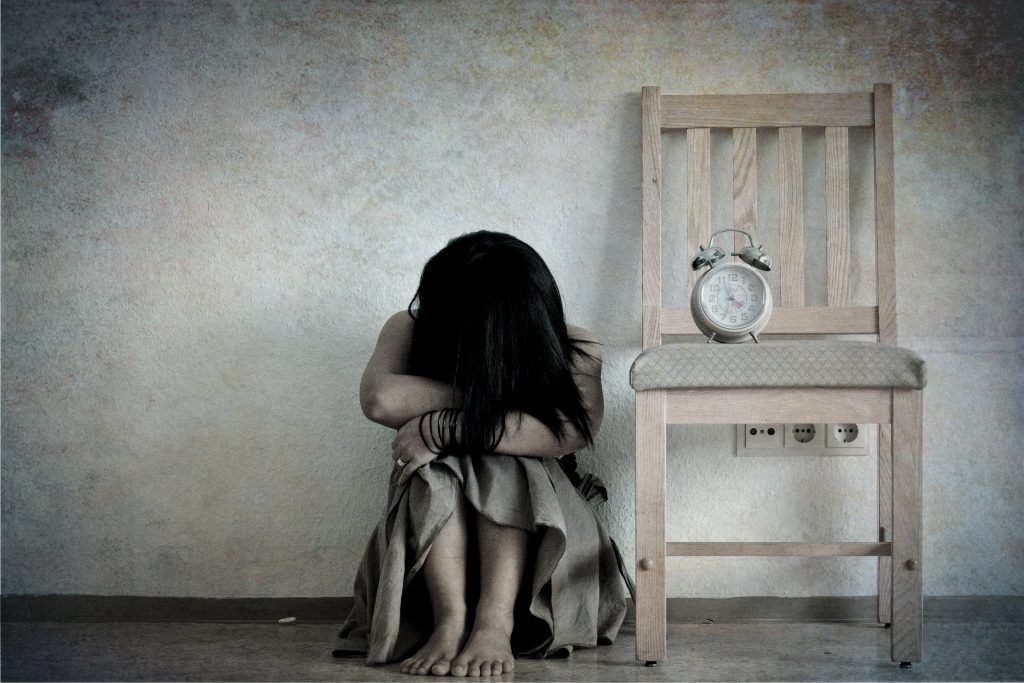 Sad girl with her head down on her knees and clock on chair, Bavaria, Germany.