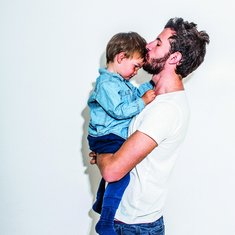 Photo portrait of father and son, isolated on white background. Father holding his son and kissing him in a forehead