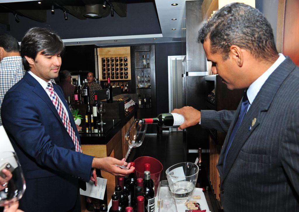Jaime Mejia sirviendo una copa de vino a Luis Laviosa