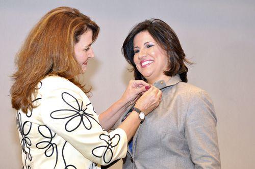 Momento en que Yasmín Darwich presidenta de la Federación de Mujeres Empresarias y Profesionales le entrega el pin a la vicepresidenta Margarita Cedeño de Fernandez.