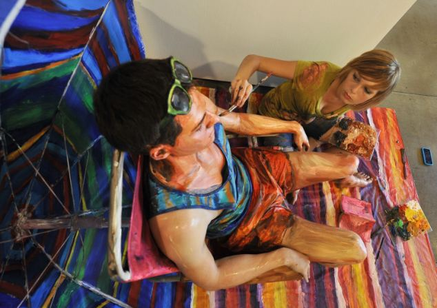 US artist Alexa Meade paints model Will Claybaugh during a performance at the Irvine Contemporary gallery in Washington on August 20, 2011. Meade, 24, paints over people so that they look like paintings, then photographs them either in a natural setting or with a painted background. AFP PHOTO/Nicholas KAMM (Photo credit should read NICHOLAS KAMM/AFP/Getty Images)