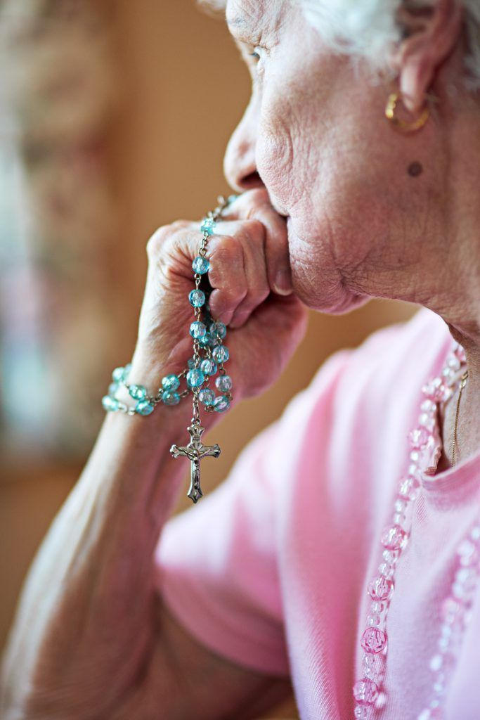 Cropped shot an elderly woman holding a rosary in prayer