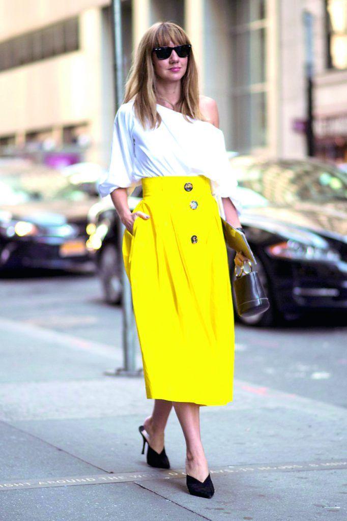 Este streetstyle combina una camisa flashdance shoulder con una midi en amarillo de zinc.